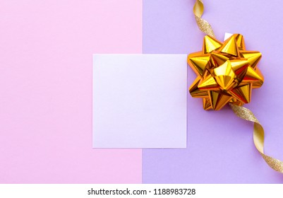 Golden bow on pink background. Festive holiday pastel backdrop. Top view, flat lay.