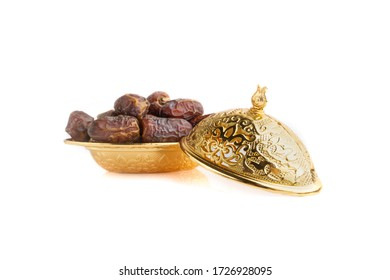Golden bowl with blurry dried dates fruits isolated on white background. Ramadan Kareem Breaking the fast by eating Tamar Dates