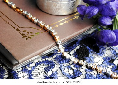 Golden bracelet with clear crystals lying on the brown book near blue flowers and silver jewelry box