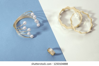Golden bracelet with pearls and zigzag shape multiple bracelets with sharp shadow on multi color paper surface