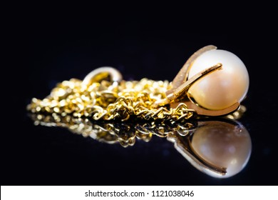 golden bracelet with white pearl in it, in front of a black background with reflection