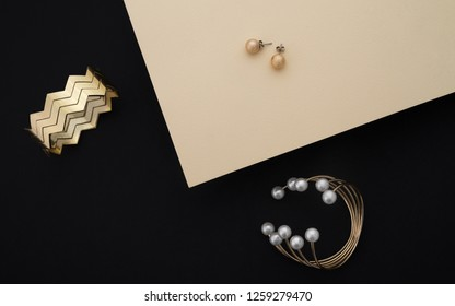 Golden Bracelets and earrings on black and beige background - Golden bracelet with pearls and zigzag shape cuff and pair of earrings on black and beige paper background