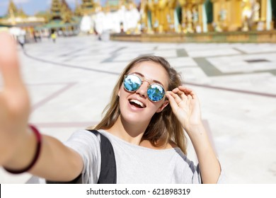 Golden bracelets Photo in low key. Vogue Style,talking to camera,laugh woman,bag,say hello,feathers in their hair, bracelets, flash tattoo, indie,Bohemia,boho style,round sunglasses,tourist background