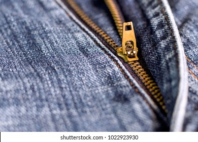 Golden brass zipper on blue jeans. selective focus. The zipper is device consisting of two flexible strips of metal with interlocking projections closed or opened.