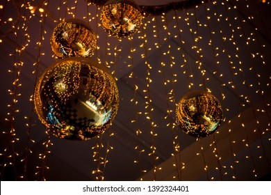 golden bright mirror balls and yellow garlands are hung on the ceiling for decoration, which give a festive atmosphere