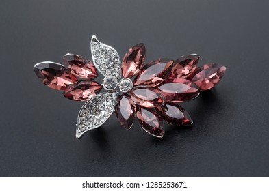 golden brooch with diamonds and rubies isolated on black
