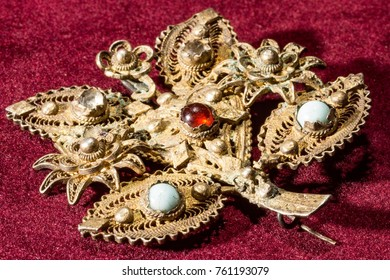 Golden brooch with gems