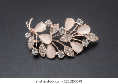golden brooch twig with moonstones and diamonds isolated on black