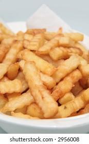 Golden brown crinkle cut fries in a plain white ceramic bowl