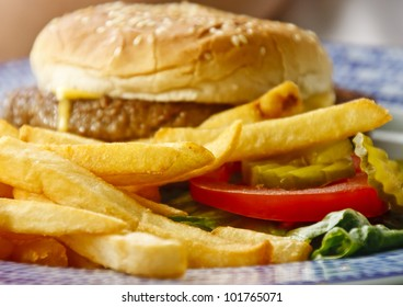 Golden brown french fries and tomato and pickle slices with cheeseburger in background