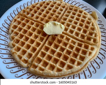 A golden brown waffle with butter.