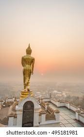 Golden Buddha standing on a mountain Wat Phra That Khao Noi, Nan, Thailand.