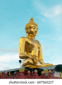 Golden Buddha statue with blue sky Thailand
