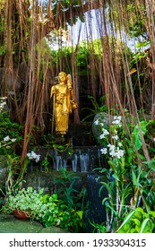 Golden Buddha statue by a stream among tropical plants, orchids and lianas, in the park of wat saket, or the golden mount temple. A landmark of bangkok city, Thailand. Vertical view.