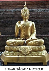 The golden Buddha statue on the old brick pagoda at the northern Thai temple.