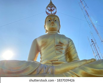 Golden Buddha statue on top of mountain in Thailand. Clear blue sky and the sun behind the statue shining bright.