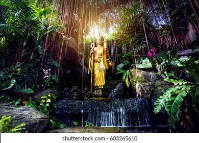 Golden Buddha statue in the tropical garden with waterfall in Wat Saket Golden Mountain Temple in Bangkok