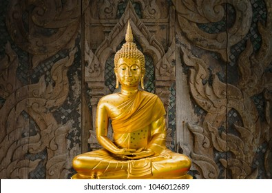 Golden buddha statue with wood carving as background