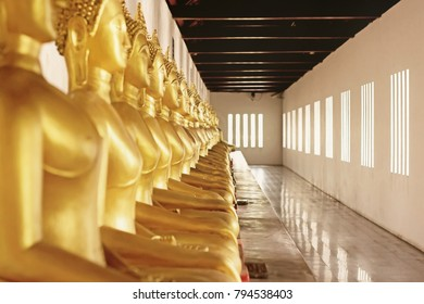 Golden Buddha statues row at Wat Phra Si Rattana Mahathat, Thailand. Perspective view of buddha statues.