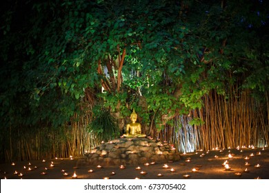 Golden Buddha under Bodhi tree among lanterns
