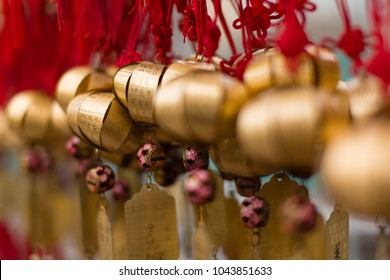 Golden buddhist prosperity bell at Wong Tai Sin temple people wish and hang them on red ropes for praying in Hong Kong. Non-English in an image means wishing for good luck in coming year.