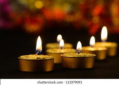Golden burning candles bokeh blured background