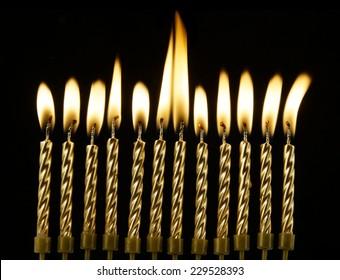 Golden burning candles on black background