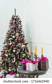 Golden candles in a candelabrum on a table with gifts boxes on a background of the Christmas tree. Gift boxes in black and silver wrapping paper with pink bows with ribbons on a white wall with stucco