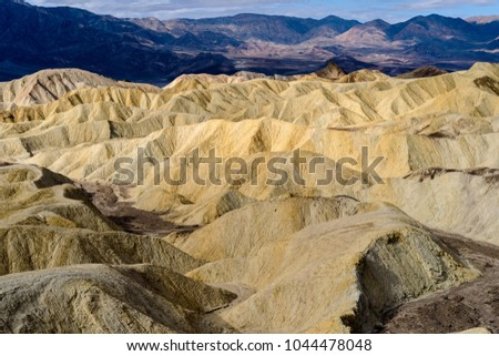 Golden Canyon - A cloudy-day overview of rolling mud stone hills, gullies and canyons at Golden Canyon of Death Valley National Park, California, USA.