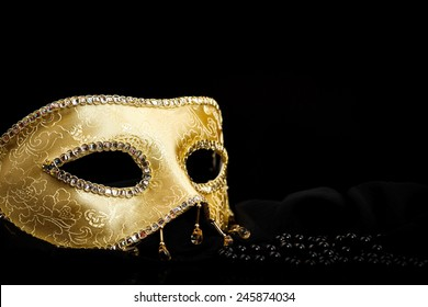 Golden carnival mask near pearls on black background
