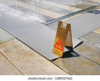 Golden Caution Wet Floor Warning Stand Near Dripping Water at the Park