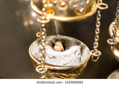 Golden chain censer with incense on burning charcoal. Close-up. During divine liturgy in Eastern Church. White clouds of fragrant smoke rise up. Selective focus. Blurred background. Vertical photo.