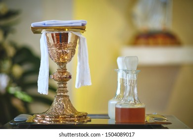 Golden chalice on the altar during mass, on a tray and other sacred objects.