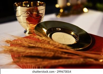 Golden chalice, golden paten, Roman missal and ear of wheat.