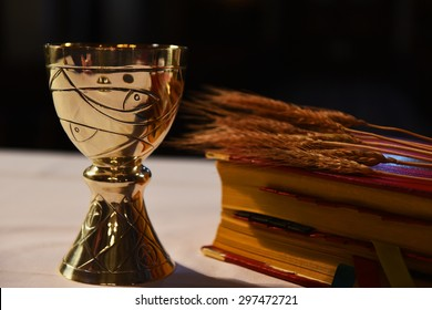 Golden chalice, prayer book and ear of wheat.