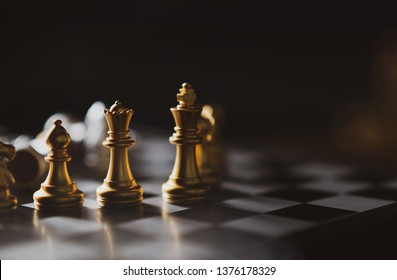 Golden Chess game King,Queen,Bishop staying on board,Business planing strong concept with dark background.