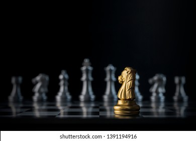 Golden chess knight is facing the silver opponent chess on black background. Leader, leadership, business strategy, challenge, brave or fearless concept.