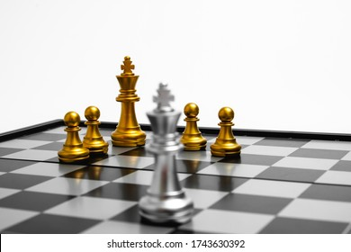 Golden chess team stand against the silver. Focus on golden king and team for Team concept.
