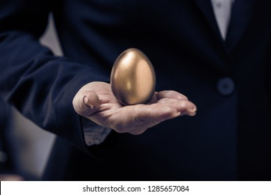 golden chicken egg in female hand closeup