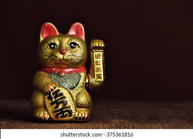 a golden chinese lucky cat with its left paw raised, on a rustic wooden surface