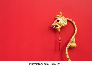 Golden Chinese style decorated dragon wand on red background