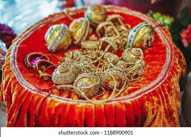 The golden Choora (Chura) and bangles on red velvet plate, the items for rituals of indian marriage ceremony
