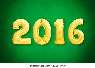 Golden Christmas 2016 sign made of inflatable balloons on green background with vignette