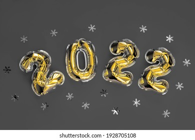 Golden Christmas 2022 balloons isolated on red background. Helium balloons, gold foil numbers. Numbers for Happy New Year 2022. Party decoration, celebration, carnival.