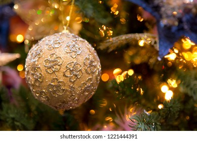Golden christmas ball with flowers hanging in the christmas tree (selective depth of field).