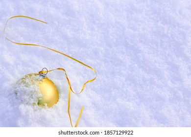 The Golden Christmas ball is forgotten and lies on the snow. Concept of completion or end of winter holidays, New Year, Christmas.