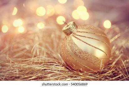 Golden Christmas ball on the background lights garland.