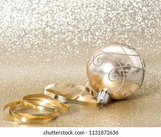 Golden christmas ball on blurred shiny background. Festive ornaments