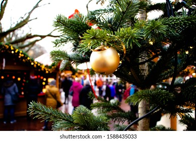Golden Christmas ball on a fir tree at the crowded Christmas market
