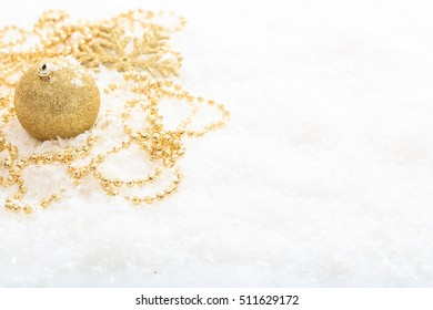 Golden christmas ball and snow on white background